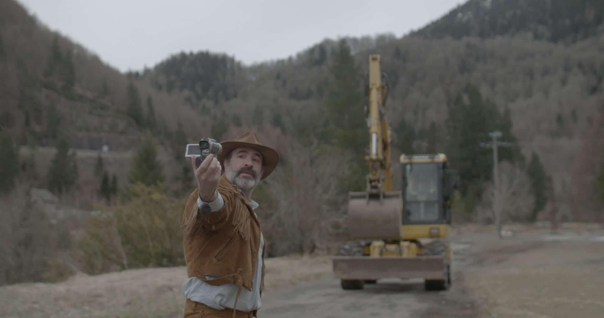 Georges (Jean Dujardin) filmt sich in Monsieur Killerstyle selbst, die Wildlederjacke und der passende Hut müssen dabei immer im Bild sein. Im Hintergrund rollt ein Bagger heran, mit dessen Hilfe er alle Jacken des Dorfes verbuddelt.