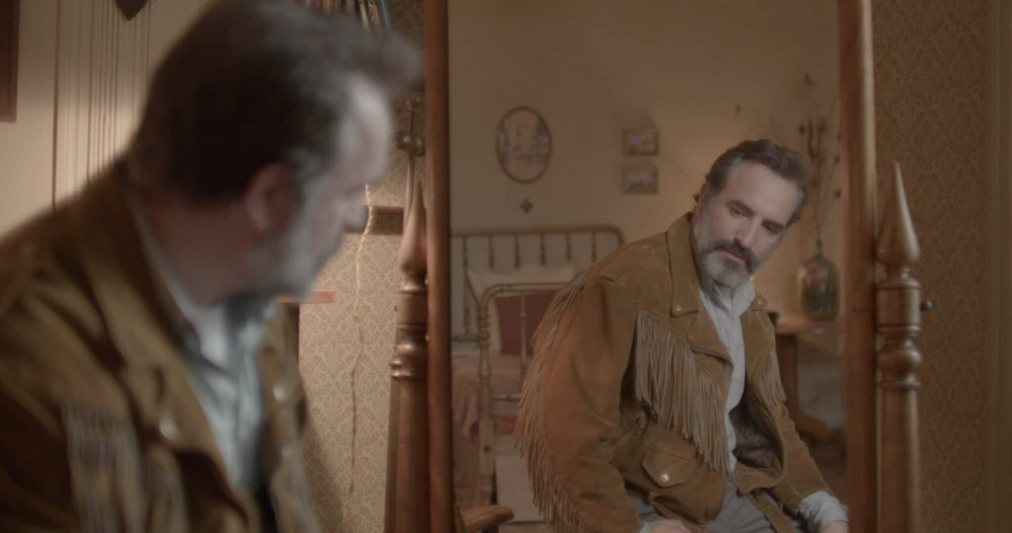 Georges (Jean Dujardin) betrachtet sich und seine neue Jacke angetan im Spiegel des Hotelzimmers in Monsieur Killerstyle.