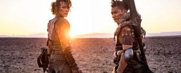 """Milla Jovovich & Tony Jaa stehen in ihren Jägermonturen Seite an Seite in einer kargen Ödnis. Beide blicken über ihre Schultern hinter sich, während im Hintergrund die Sonne hinterm Horizont verschwindet. - """"Monster Hunter"""""""