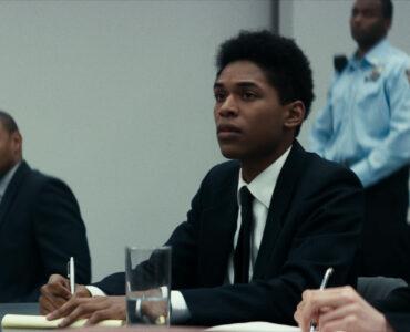 Im Gerichtssaal sitzt Steve neben seiner Anwältin. Links im Bild sitzt ein weiterer Angeklagter mit seinem Verteidiger. Alle tragen schwarz, nur der Polizist im Hintergrund hat ein blaues Hemd an inMonster! Monster? ist das Regiedebüt eines Musikvideomachers, das von einem Mordangeklagten und dessen Fall vor Gericht erzählt..