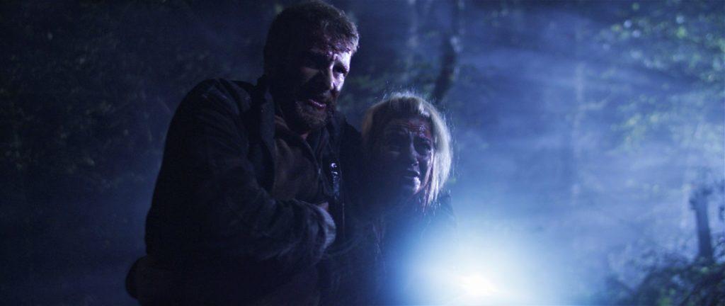 Die Protagonisten in Mutant River - Blutiger Alptraum blicken vor nebelverhangener Waldkulisse verängstigt drein.