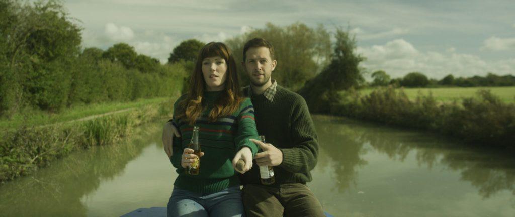 Kat (Kate Marie Davies) und ihr Lebensgefährte Marl (Mark McKirdy) durchfahren am Steuer des Bootes einen Kanal.
