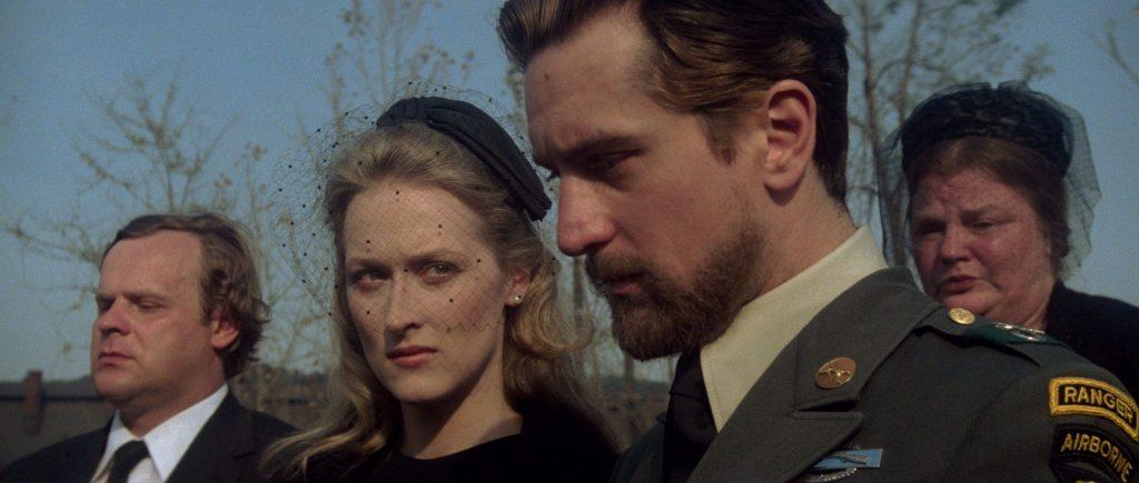 Steve und seine Frau (Meryl Streep) bei einer Beerdigung, beide tragen schwarz, schauen traurig, um sie viele Leute