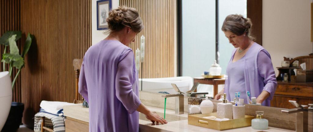 Mariannes Mutter schaut entsetzt auf das grüne Wasser, das aus der Luxus-Amatur des Badezimmers strömt - New Order