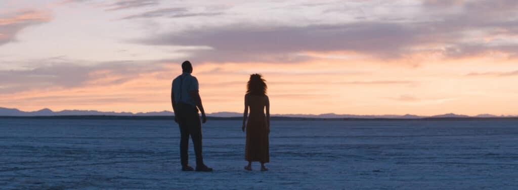 Will (Winston Duke) und Emma (Zazie Beetz) blicken gemeinsam am Strand auf die Dämmerung