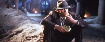 Peter Weller sitzt als Bill Lee auf einem Sandhaufen in einem Hof in Tanger in Naked Lunch.