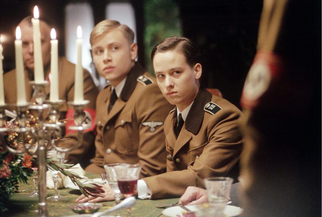 Friedrich und Albert sitzen mit braunen Uniformen am festlich gedeckten Tisch mit Kerzenleuchter.