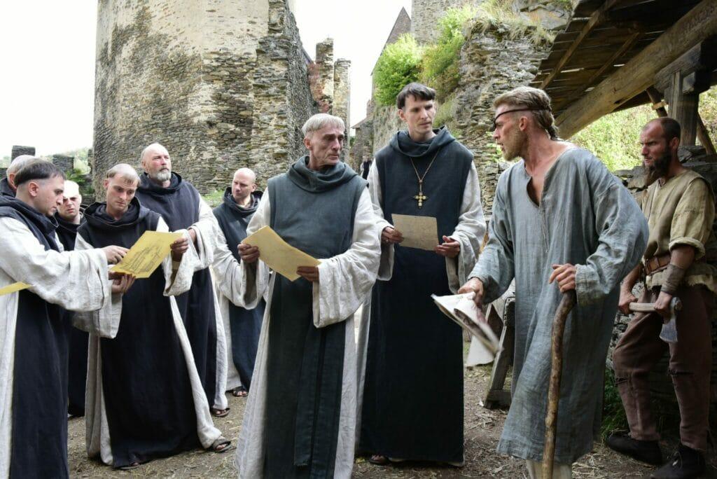 Narziss und Goldmund im Gespräch mit Mönch Lothar. Goldmund trägt ein langes graues Gewand und lehnt auf einer Krücke. Dabei schaut er in erster Linie die vor ihm stehenden Narziss und Lothar an. Die drei halten ein gelbliches Papier in der Hand, genauso wie die weiteren Mönche, die im Hintergrund stehen.