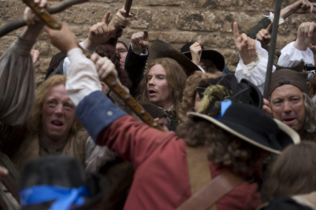 Ned (Joe Dempsie) inmitten einer aufgebrachten Menschenmenge ©Tiberius Film