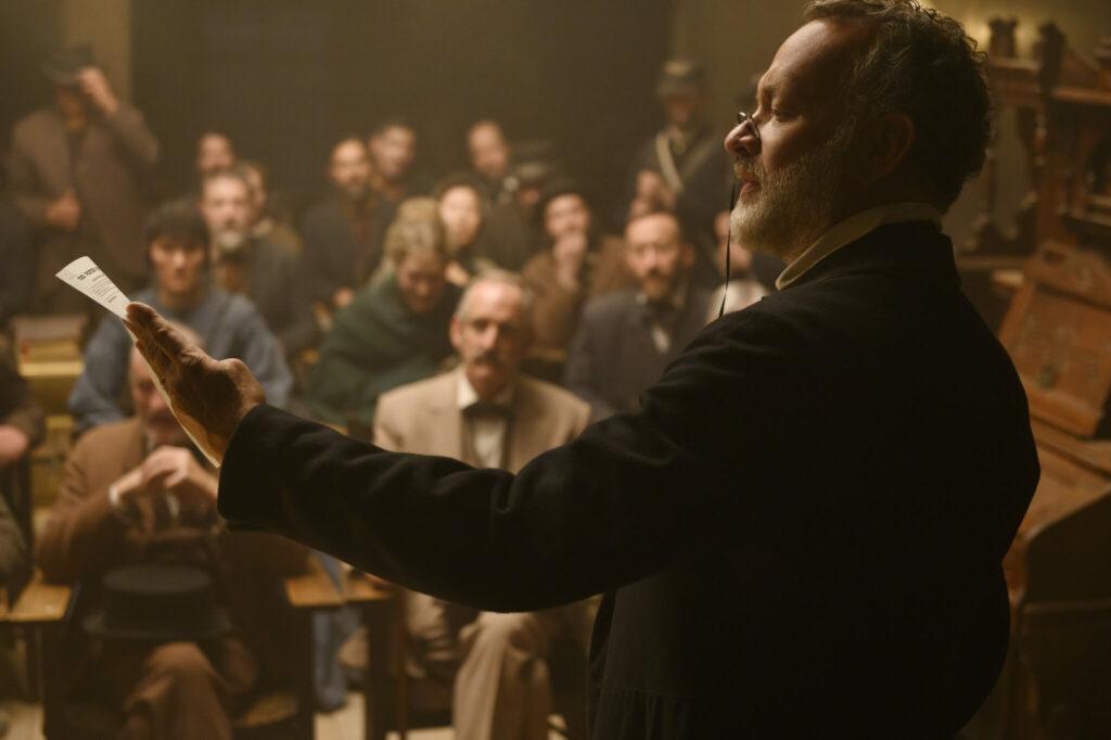 Tom Hanks hält in seiner Hand eine Zeitung und liest dem lauschenden Publikum daraus vor.