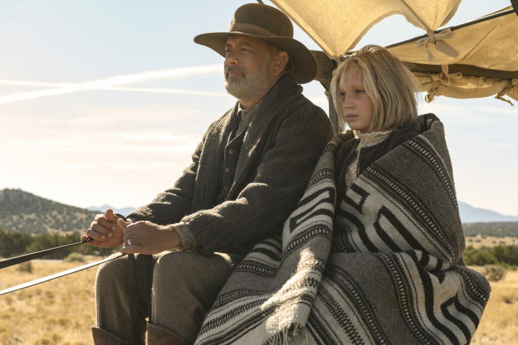 Tom Hanks und Helena Zengel sitzen auf einer Kutsche und schauen in die Ferne.
