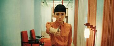 Nina Wu (Wu Ke-Xi) läuft mit starren Blick direkt in die Kamera gerichtet in orangenfarbenen Kleid und gezücktem Messer einen engen Gang entlang.