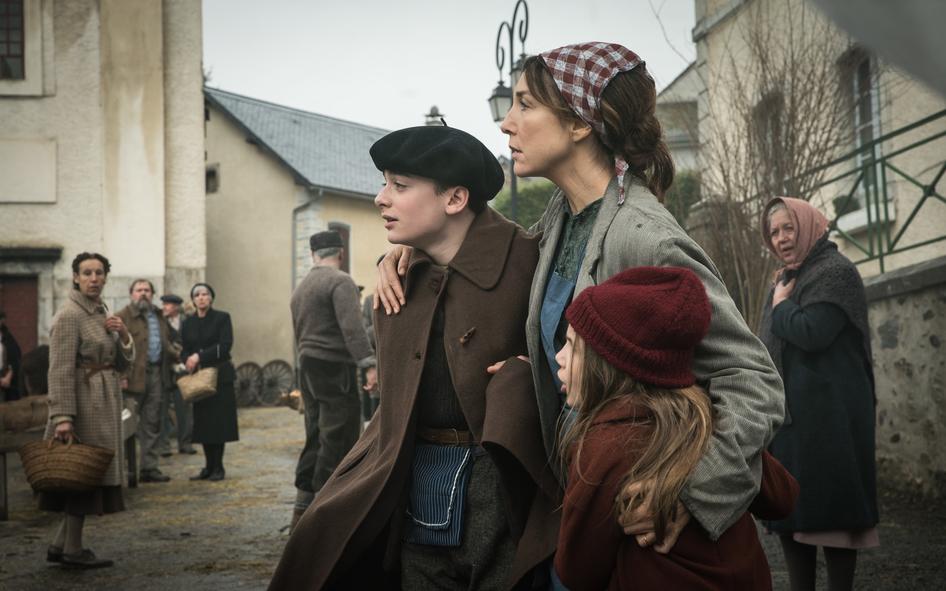 Jo, gespielt von Noah Schnapp, seine Mutter, gespielt von Elsa Zylberstein, und seine Schwester beobachten in Nur ein einziges Leben den Einmarsch deutscher Soldaten.