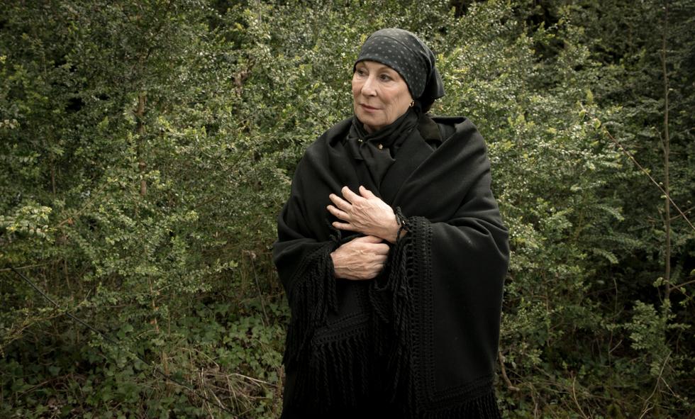 Horcada, gespielt von Anjelica Huston, steht im Wald und beobachtet besorgt die Soldaten.