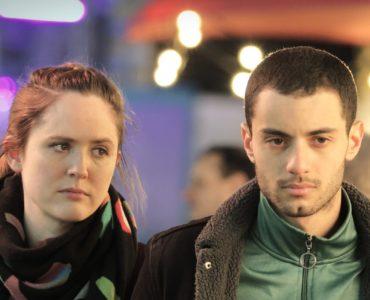 Lilly und Karim laufen in Nur ein Augenblick über einen Jahrmarkt - die schwierige Vergangenheit ist ihnen ins Gesicht geschrieben.