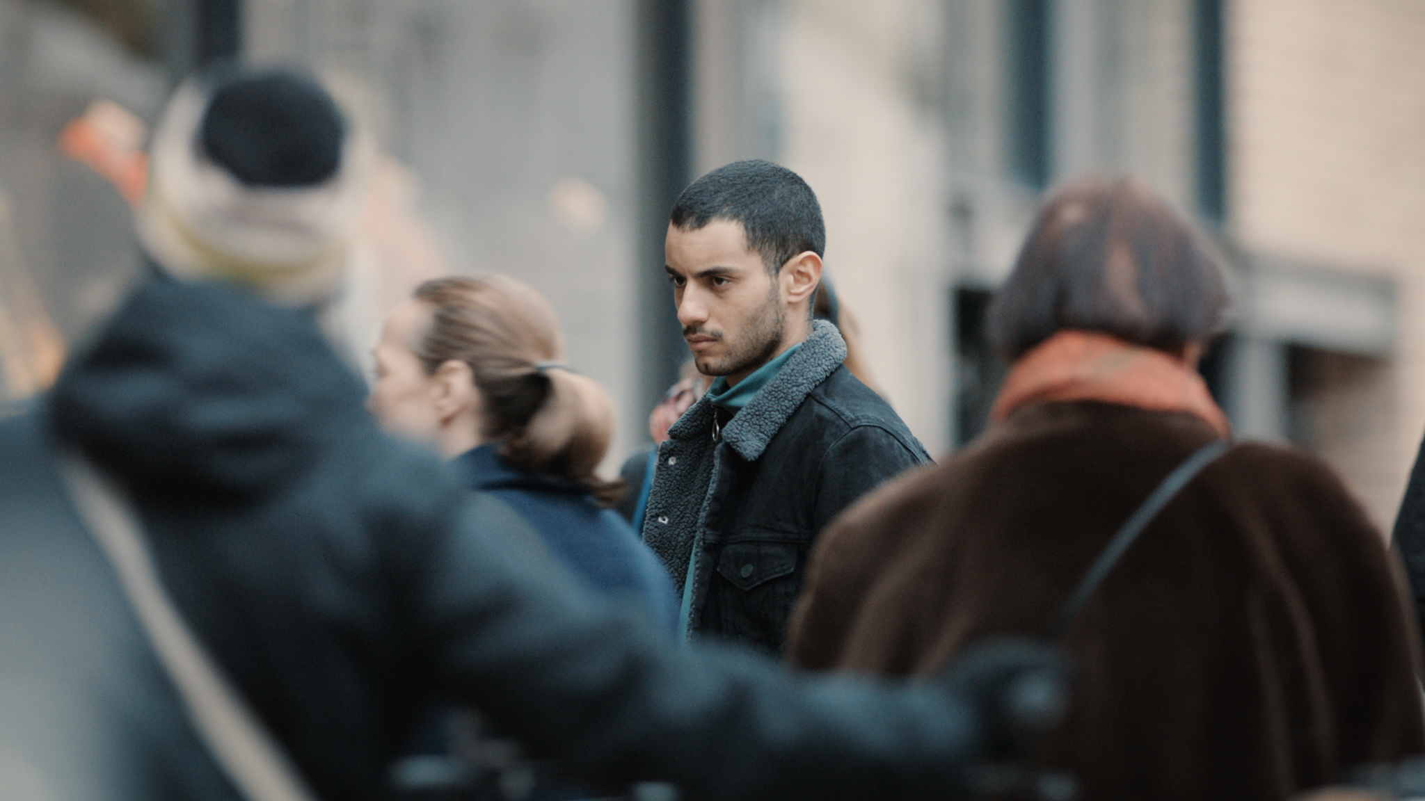 Karim steht mit ernstem Blick im Zentrum des Bildes in Nur ein Augenblick. Die Passanten um ihn herum sind unscharf.