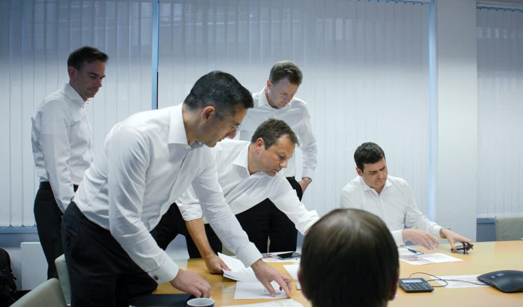 Investment-Banker in weißen Hemden disskutieren über einem Holztisch und schauen auf die ihnen vorliegenden Unterlagen