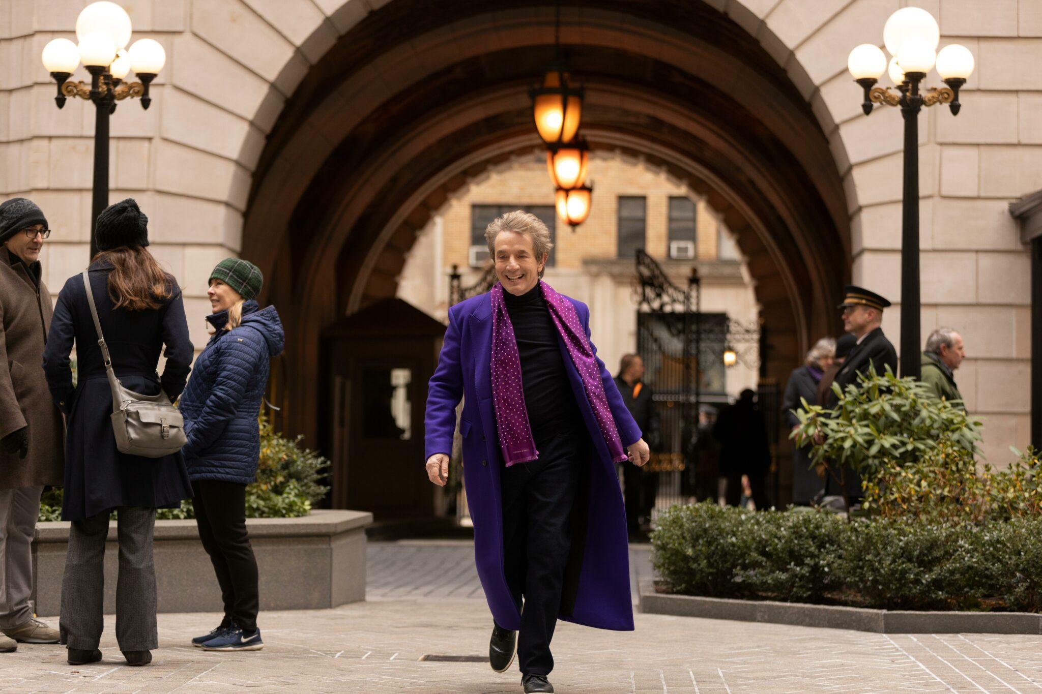 Oliver (Martin Short,) mit einem violetten Mantel und pinken Schal, läuft freudestrahlend in Richtung Kamera. Im Hintergrund sieht man einige Passanten sowie einen Torbogen und zwei Laternen.