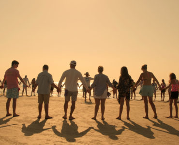 Eine große Gruppe von Bewohnern bilden eine Menschenkette am Strandder Outer Banks