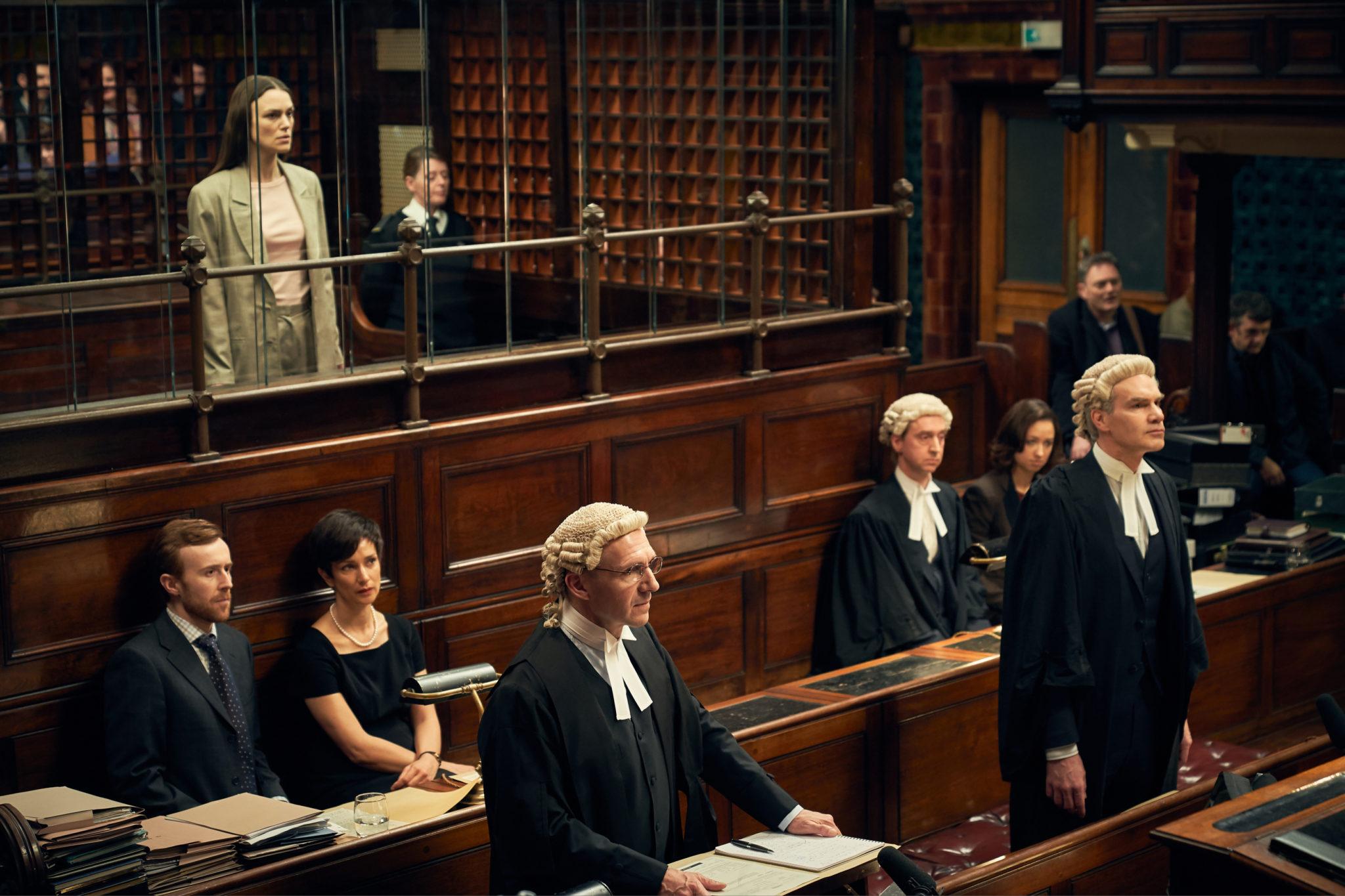 Im klassisch braunen Gerichtssaal steht die wegen Verstoß gegen den Official Secrets Act Angeklagte Katharine Gun (Keira Knightley) im Hintergrund, Verteidiger Ben Emmerson (Ralph Fiennes) im Vordergrund.