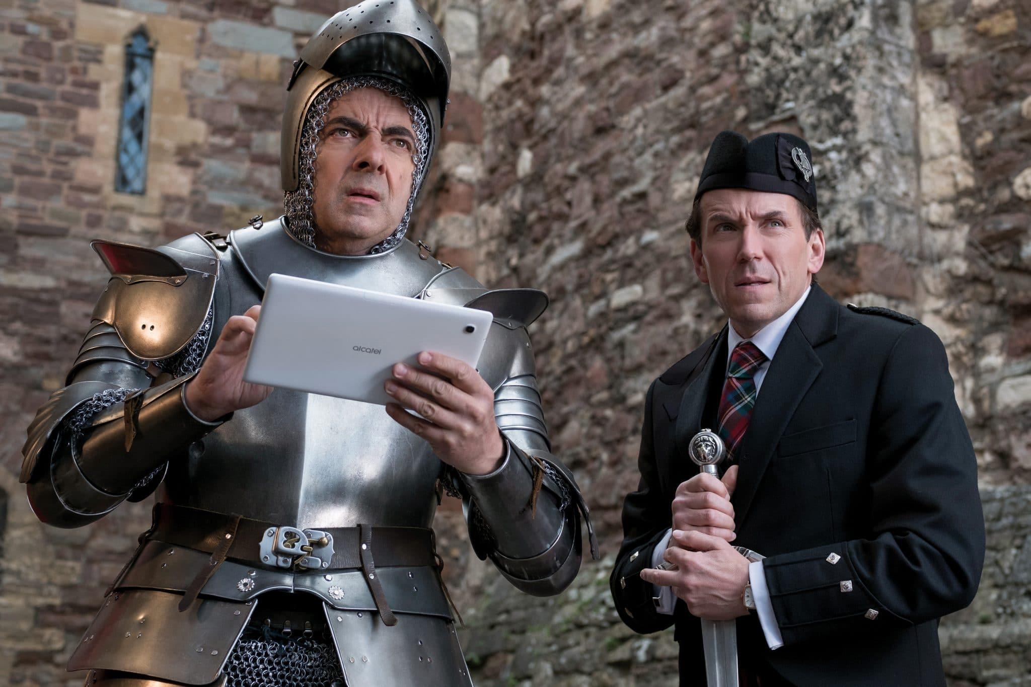 Johnny English (Rowan Atkinson) hält ein Tablet in seinen Händen während er eine Ritterrüstung trägt. Neben ihm steht sein Partner Rough (Ben Miller) in Uniform mit Schwert in den Händen.