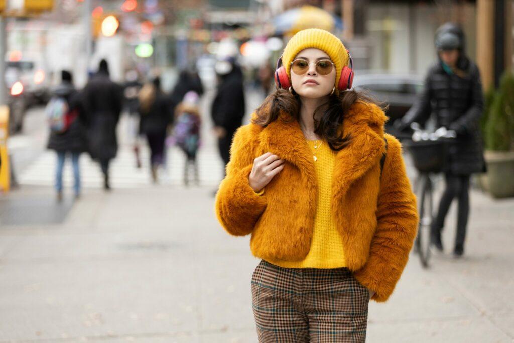 Zu sehen ist Selena Gomez als Mable. Sie trägt ein schrilles Outfit - ein gelben Strickpullover, darüber eine orange Pelzjacke sowie eine karierte Hose und Fliegerbrille. Passend dazu trägt sie einen gelben Beanie auf dem Kopf und große rote Kopfhörer.