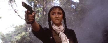 Sue (Joyce Godenzi) hält in Operation Eastern Condors mit ernstem Blick eine Pistole in der rechten Hand und visiert ein Ziel an.