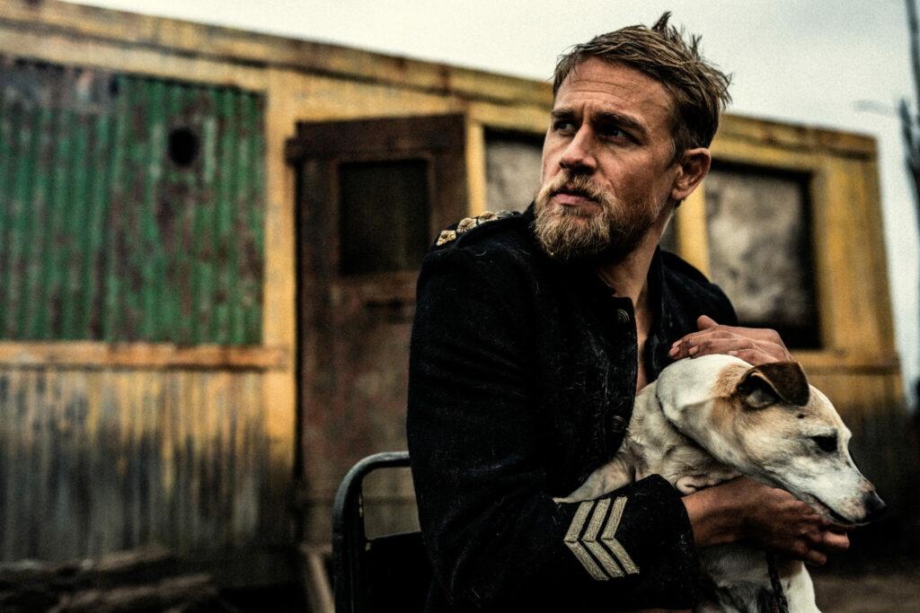 """In """"Outlaws - Die wahre Geschichte der Kelly Gang"""" spielt Charlie Hunnam Sgt. O'Neill, der hier in seiner dunkelblauen Uniform vor einem gelblichen Gebäude sitzt, welches wie ein Container wirkt. Er hält in seinen Armen einen weißen Hund und blickt sorgenvoll nach rechts."""