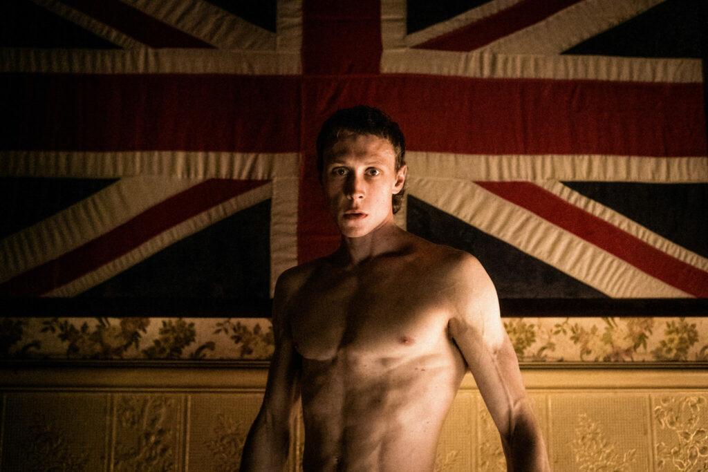 """George MacKay verkörpert die Hauptfigur von """"Outlaws - Die wahre Geschichte der Kelly Gang"""" Ned Kelly. MacKay steht breitschultrig mit freiem und gestählten Oberkörper vor einer britischen Flagge, die an einer Wand hängt.Sein Blick trifft den Betrachter und ist durchdringend."""