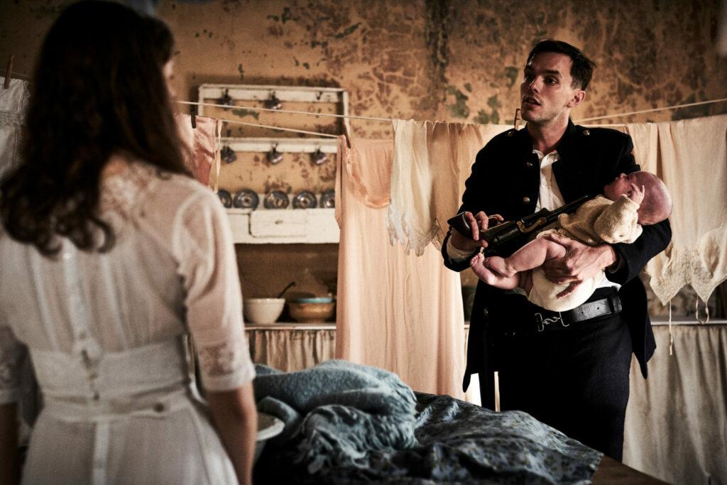 """Nicholas Hoult spielt in """"Outlaws - Die wahre Geschichte der Kelly Gang"""" den fiesen Constable Fitzpatrick, der hier eine Waffe auf ein Baby richtet. Er hält dabei das Baby auf dem Arm, während er dessen Mutter (Thomasin McKenzie) gegenübersteht."""
