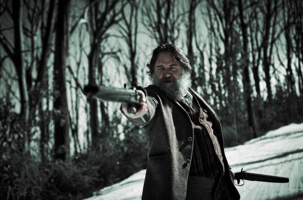 """In """"Outlaws - Die wahre Geschichte der Kelly Gang"""" spielt Russell Crowe den berüchtigten Bushranger Harry Power. Auf dem Bild steht er in einer verschneiten Landschaft, im Hintergrund sind Bäume zu sehen. Crowe trägt längeres Haar und einen grauen Rauschebart. Er hält in der rechten Hand eine Feuerwaffe mit langen Lauf und richtet diese auf jemanden außerhalb des Bildes."""