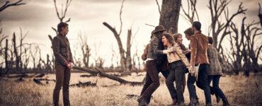 Auf dem Bild sieht man die karge Ödnis in der Ned Kelly aufgewachsen ist. Aus trockener Erde ragen kahle Bäume heraus. Ned Kelly steht links im Bild mit verschränkten Händen. Auf der rechten Seite steht Neds Familie, die die aufgebrachte Mutter Kelly zurückzuhalten versuchen.