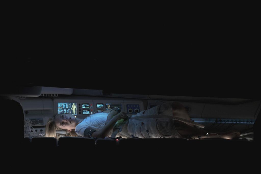 Elizabeth Hansen (Mélanie Laurent) liegt flach auf dem Rücken in einer Kryokapsel. Im Hinergrund leuchten Anzeigen