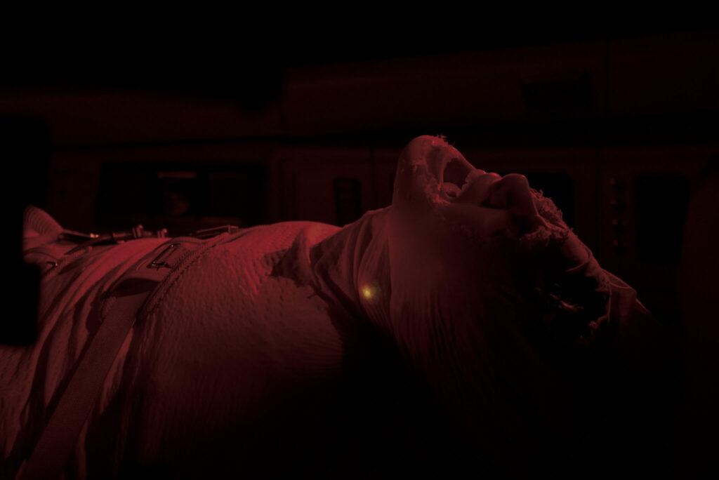 Eine gefesselte und komplett verbundene Person erwacht schreiend aus dem Kryoschlaf