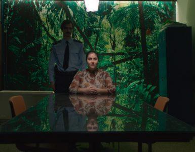 Petrunya sitzt auf der Polizeiwache. Zwischen ihr und der Dschungel-Tapete steht ein Polizist.