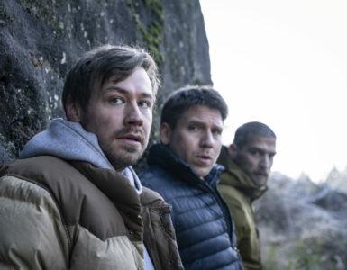 Man sieht die drei Teilnehmer des Junggesellenabschieds Roman, Albert und Peter nebeneinander an einer Felswand stehend.
