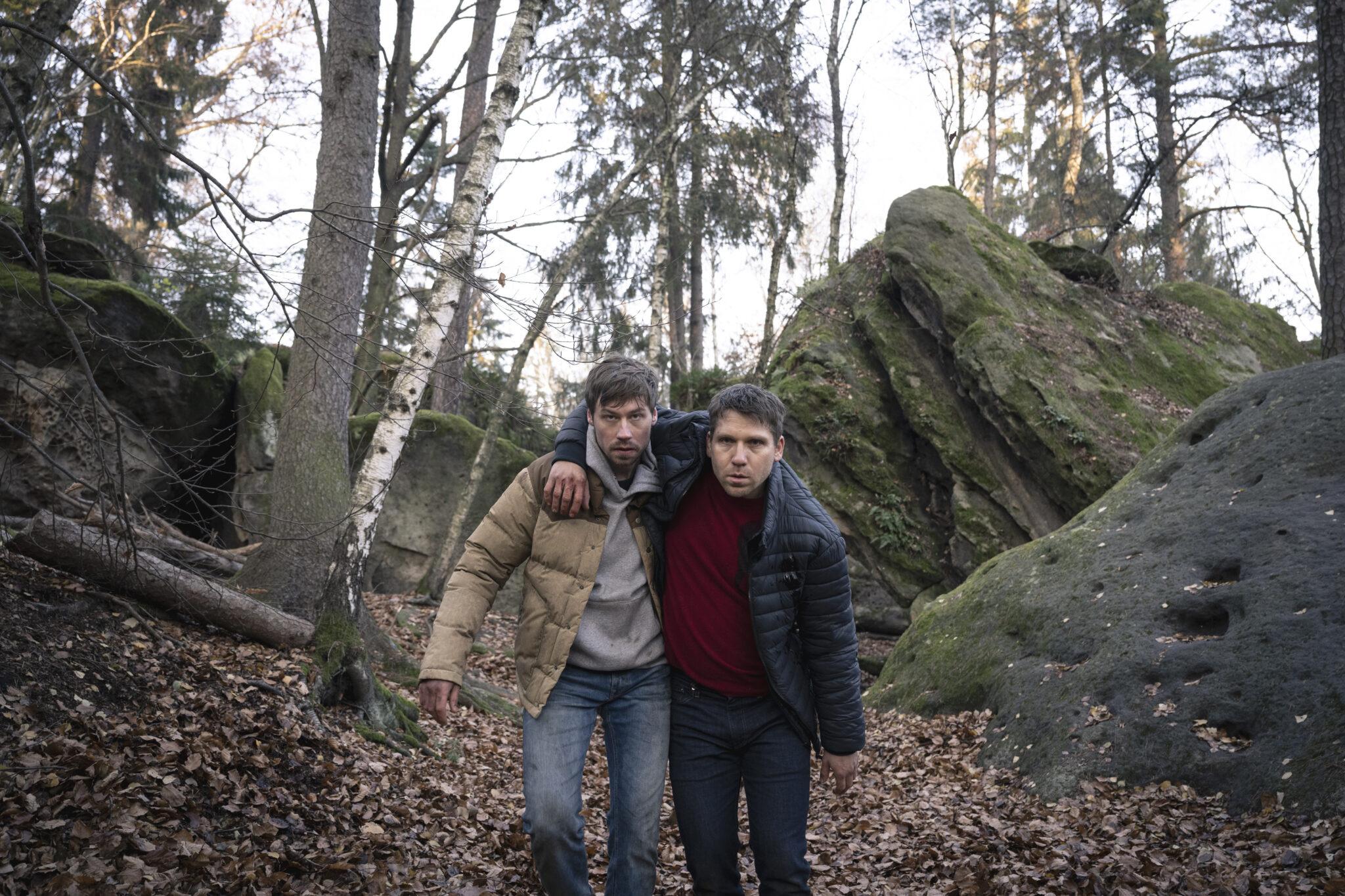 Roman (David Kross) stützt seinen verletzten Bruder Albert (Hanno Koffler) während die beiden durch den Wald laufen. Im Hintergrund sieht man kahle Bäume und große Felsen, der Boden ist laubbedeckt.