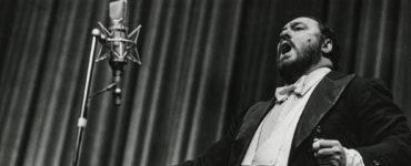 Pavarotti singt im Stehen inbrünstig eines seiner ausgewählten Stücke. Das Bild ist in Schwarz-Weiß gehalten.