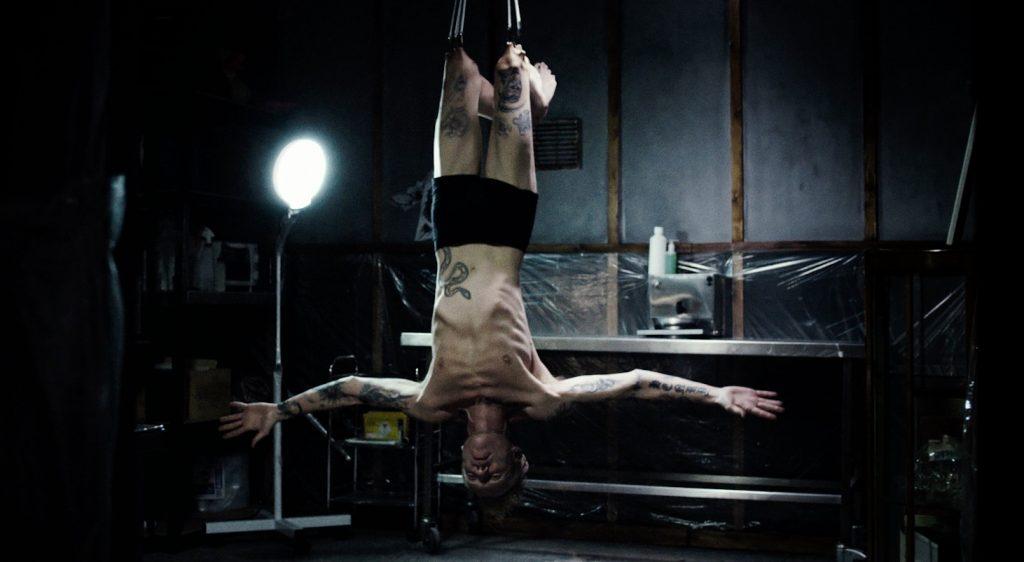 Richard Brake hängt als Tattoowierer mit Knien am Haken.
