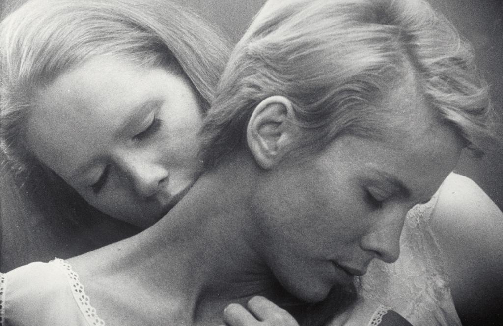 Elisabet Vogler (Liv Ullmann) schmiegt sich an Alma (Bibi Andersson) und küsst ihren Nacken. Beide haben die Augen zu und es scheint, als würden sie den Moment genießen.