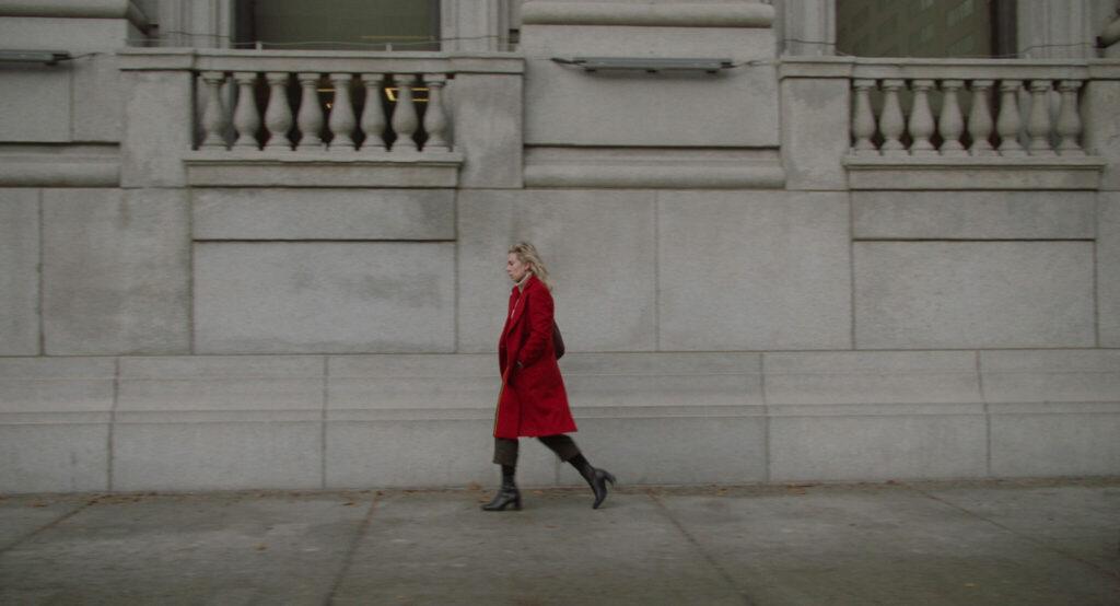 Vanessa Kirby trägt einen roten Mantel und läuft die Straße entlang
