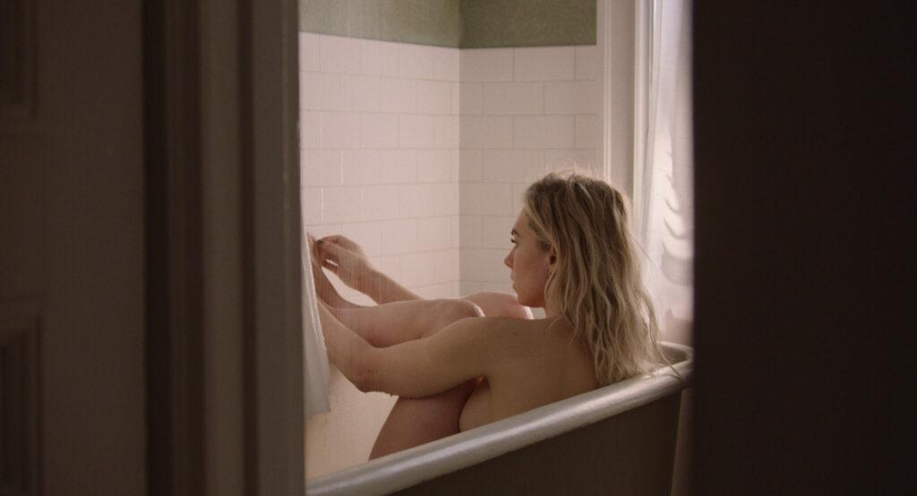Vanessa Kirby sitzt in der Badewanne und mustert zusammengepfercht ihre Zehen