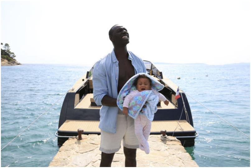 Plötzlich Papa - Omar Sy steht auf einem Bootsteg am Meer und hält sein Baby in Händen