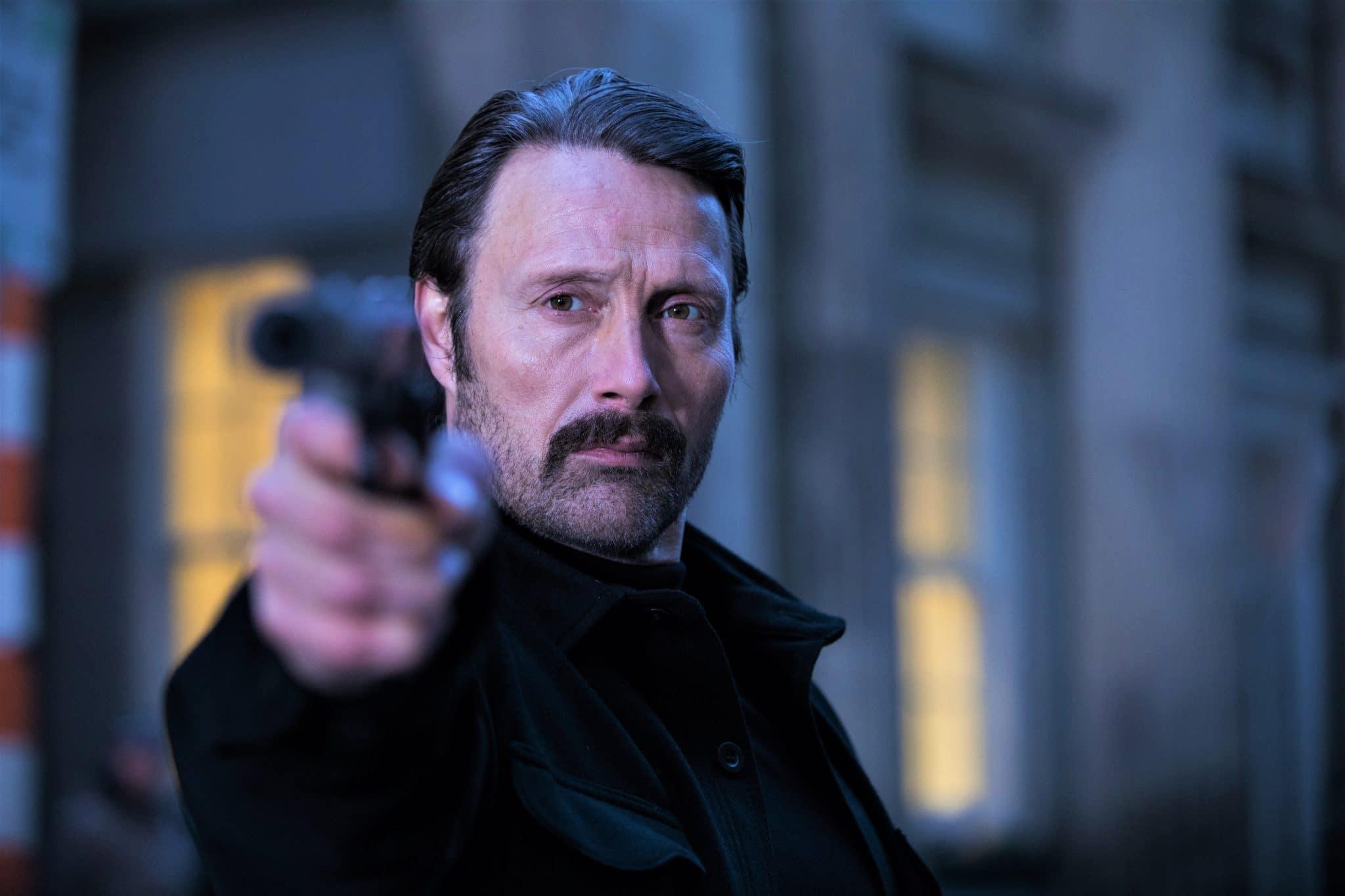 Black Kaiser (Mads Mikkelsen) ganz in Schwarz, zielt mit einer Pistole auf eine nicht zu sehende Person.