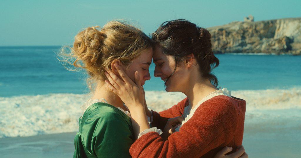 Marianne zieht Héloïse am Strand an sich heran. Beide wissen, dass ein ersehnter Kuss auch ein verbotener Kuss wäre | Porträt einer jungen Frau in Flammen