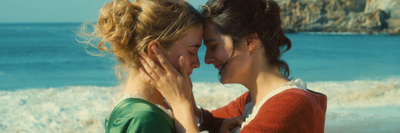 Marianne zieht Héloïse am Strand an sich heran. Beide wissen, dass einersehtner Kuss auch ein verbotener Kuss wäre | Porträt einer jungen Frau in Flammen