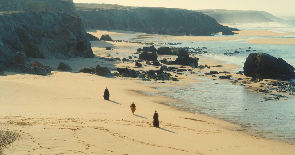 Marianne, Héloïse und ihre Freundin Sophie wandern am Strand. Sophie rennt dabei zwischen den beiden Frauen umher. Es ist teil eines wichtigen Rituals. | Porträt einer jungen Frau in Flammen
