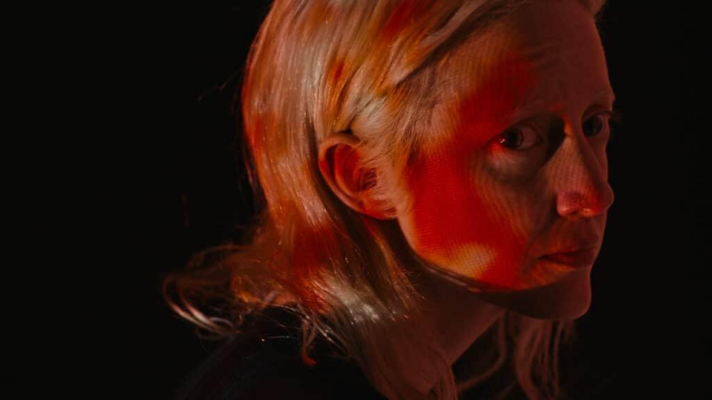"""""""Possessor"""" ist Thema im Filmtoast Adventsfrühstück Podcast #4. Andrea Riseborough, die Hauptdarstellerin von Possessor, schaut vom Neonlicht umhüllt provokant in die Kamera."""