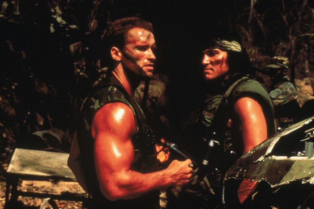 Arnold Schwarzenegger als Dutch und Sonny Landham als Billy Sole stehen in Predator mit Waffen bepackt im Dschungel