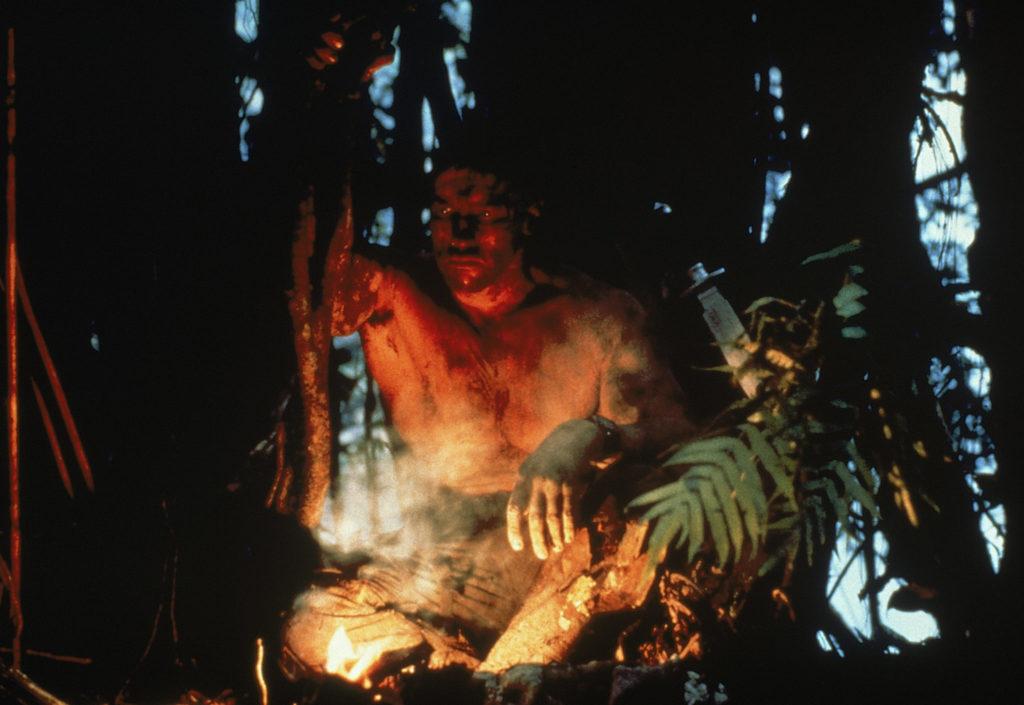 Arnold Schwarzenegger bereitet sich vor einem Feuer sitzend auf seinen letzten entscheidenden Kampf gegen den Predator vor
